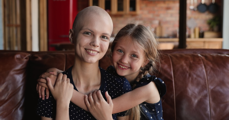 Little adorable loving daughter hug young bald mother cancer patient. Caring small kid girl express love embrace mom sit together on couch. Oncology disease remission, happy kid supporting mum concept Royalty-Free Stock Footage #1066385341