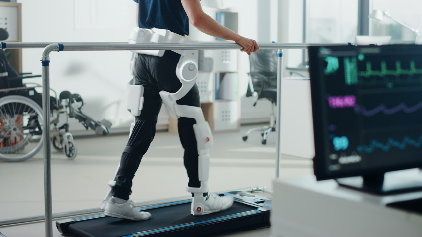 Modern Hospital Physical Therapy: Patient with Injury Walks on Treadmill Wearing Advanced Robotic Exoskeleton Legs. Physiotherapy Rehabilitation Technology to Make Disabled Person Walk. Focus on Legs Royalty-Free Stock Footage #1066412722