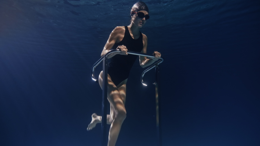 Cinematic shot of young female athlete with muscular body is exercising with effort and determination on stationary treadmill machine underwater.Concept of sport, fitness, healthy lifestyle,recreation | Shutterstock HD Video #1066429186