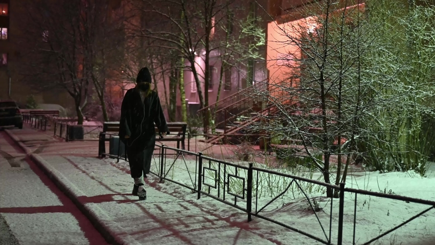 A girl walks at night during a snowfall on the sidewalk of a residential neighborhood of the city, in a black mask, in winter clothes, parked cars, the light from street lamps.