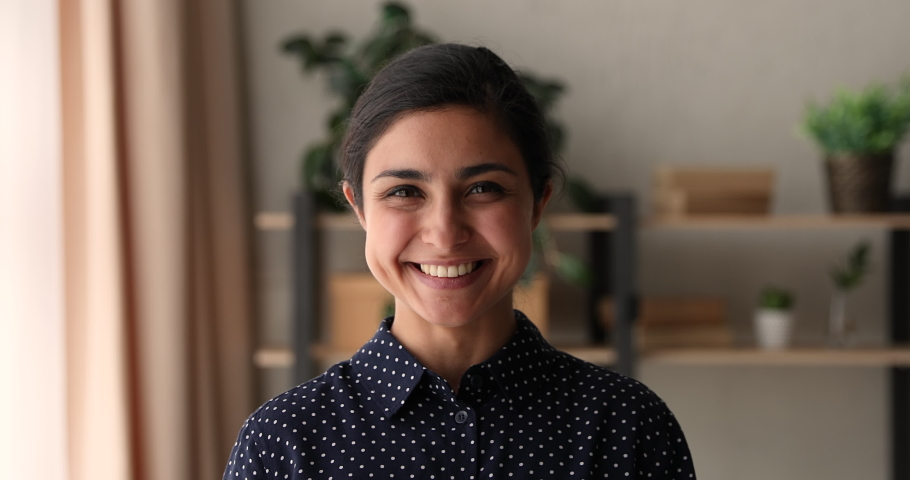 Head shot positive attractive millennial indian ethnicity business lady or company representative looking at camera, feeling confident indoors. Happy mixed race woman showing perfect wide smile. | Shutterstock HD Video #1066471510