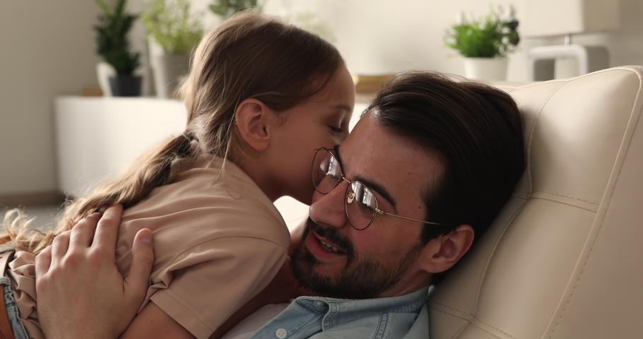 Little daughter whispers in ear confides a secret to daddy, close up. Loving dad talk to small child, family enjoy communication sit at home on chair. Harmonic friendly relation, understanding concept