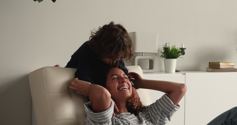 Little boy cuddling tickling loving mom seated on leather chair at home, family enjoy playtime together, play game laughing feel carefree. Happy motherhood, babysitting, communication with kid concept