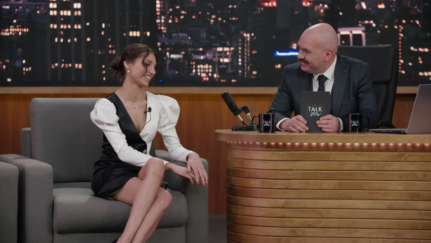 ZOOM IN Late-night talk show having a conversation greeting celebrity guest in a studio. TV broadcast style show. Shot with RED cinema camera Royalty-Free Stock Footage #1066500478