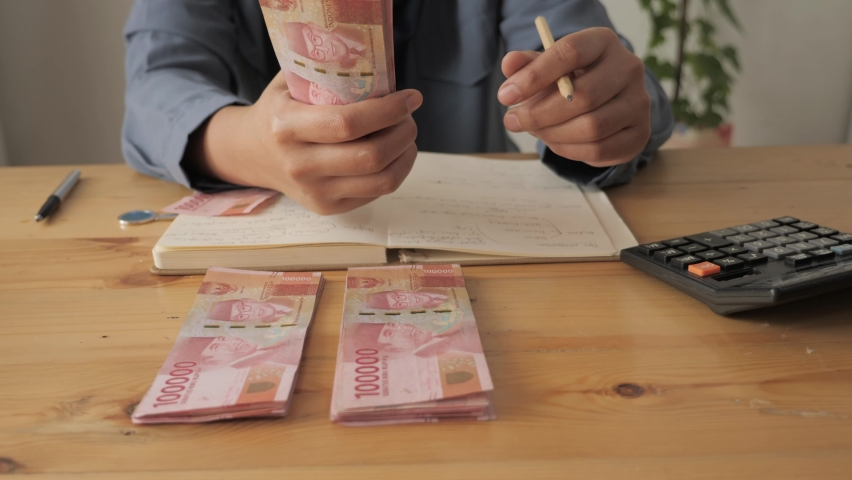 Close up of woman hand counting money uang Indonesian rupiah and making notes, money financial management concept Royalty-Free Stock Footage #1066547614