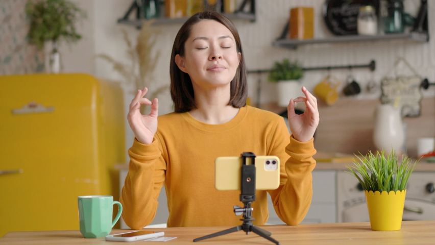 Mindful calm beautiful mixed race female blogger making video lessons and tutorials for internet vlog website classes sit at sofa doing yoga breath exercise meditate at home, harmony and balance state Royalty-Free Stock Footage #1066547773