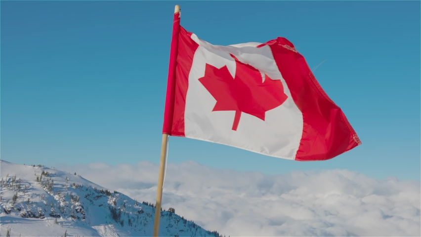 Canadian Flag with a winter mountain landscape in the background. bright and sunny morning. Taken in Whistler, British Columbia, Canada. Slow Motion