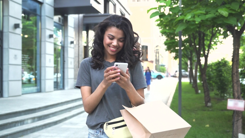 Smiling happy young adult African American woman shopper customer standing on city street holding shopping bags and smart phone using mobile fashion sale e commerce app near shop, mall or store. Royalty-Free Stock Footage #1066593484