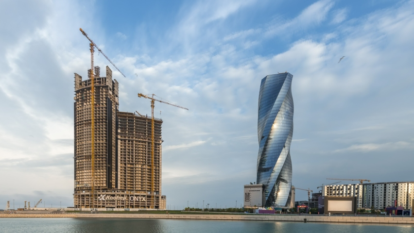Manama, Bahrain February 01, 2021 - 4K Time lapse of an under construction building and Untied Tower with beautiful moving clouds