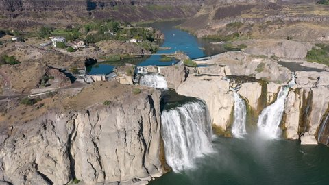 Drone camera tracking across the Shoshone Falls with the Snake River and houses in the background.