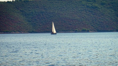 Lone Sailboat Sailing In The Tropical Sea With Incredible Lush Green Mountains View - Wide Shot