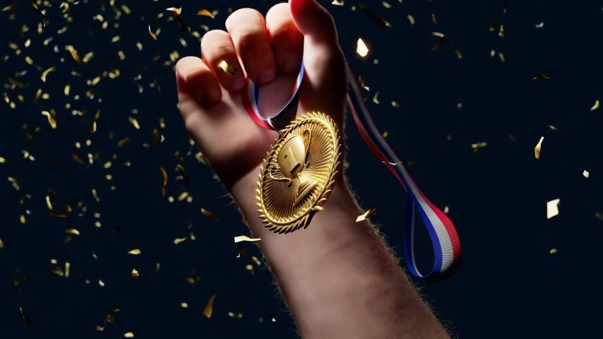 Rising hand holding a shiny gold medal. Top winner with first prize. Sports award for a champion. Winning a competition. Success, victory, triumph. Moment of glory. The greatest achievement. Confetti. Royalty-Free Stock Footage #1066662892