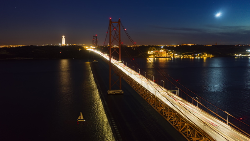 Drone flying over Ponte 25 de Abril at night, Lisbon, Portugal, Europe. Aerial view of cars driving on bridge in night time. Suspension bridge over Tagus river in Lisbon. 4k footage in hyperlapse   Shutterstock HD Video #1066668253
