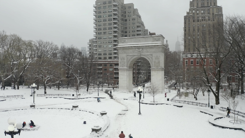 Rising aerial over Washington Square Park arch white winter snow - blizzard snowing in NYC