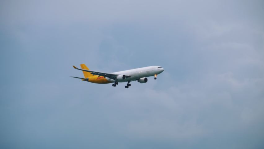 CHANGI, SINGAPORE - NOVEMBER 25, 2018 : Airbus A330 airfreighter DHL livery approaching, with cloud burst and condensation, before landing in Changi Airport, Singapore | Shutterstock HD Video #1066712002