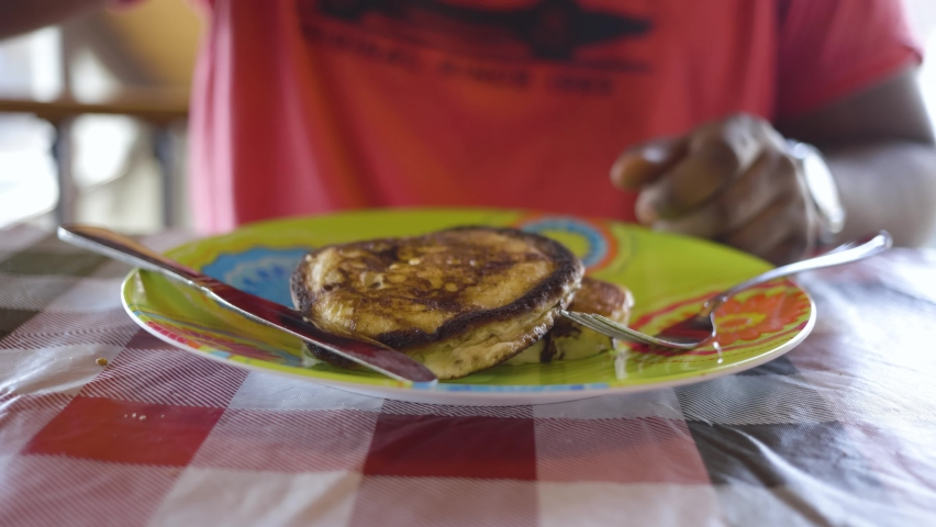 close up view of fluffy golden buttermilk pancakes having maple syrup poured slowly over them by an African American male. the homemade breakfast recipe is delicious meal for the morning  Royalty-Free Stock Footage #1066722427