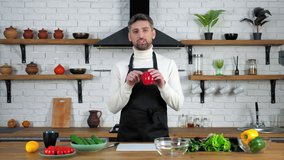 Man chef food blogger in black apron looking camera tells teaches records remote online video culinary webinar master class course in home kitchen, vegetables ingredients cooking salad on table