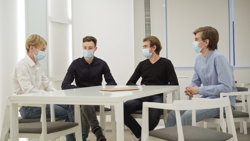 Positive millennial coworkers in coronavirus face masks touching elbows making deal in office conference room. Successful Caucasian colleagues talking discussing startup. New normal Covid-19 lifestyle Royalty-Free Stock Footage #1066760041