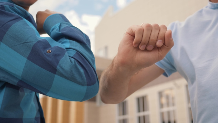 Elbow greetings on street. Social distance. Prevention of coronavirus infection. Two business man greet with elbows from distance. Coronavirus safety. Social distance elbow greetings. Two business man Royalty-Free Stock Footage #1066760794