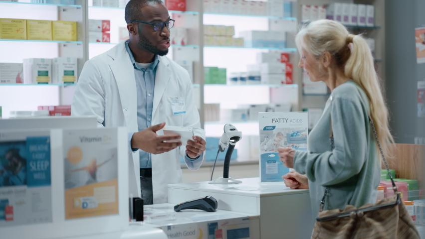 Pharmacy Drugstore Checkout Counter: Black Male Pharmacist Explains Use and Manual for Prescription Medicine Beautiful, Senior Female Customer Paying Using Contactless Credit Card to Terminal Royalty-Free Stock Footage #1066836151