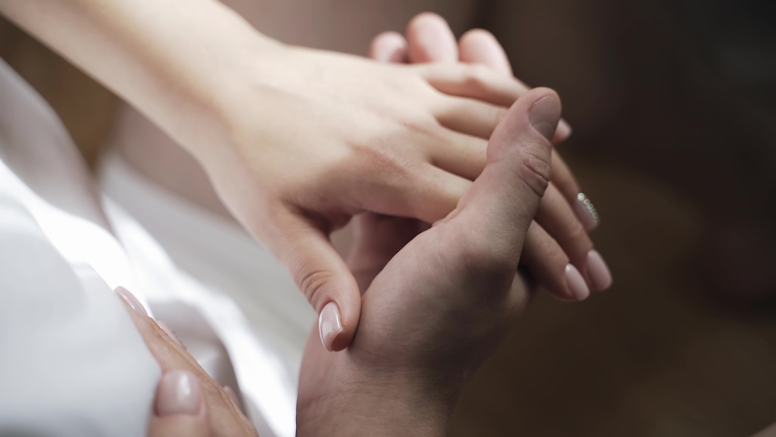 The man gently holds his beloved's hand in his own and gently strokes it with his fingers. Shooting lovers ' hands in close-up Royalty-Free Stock Footage #1066842877