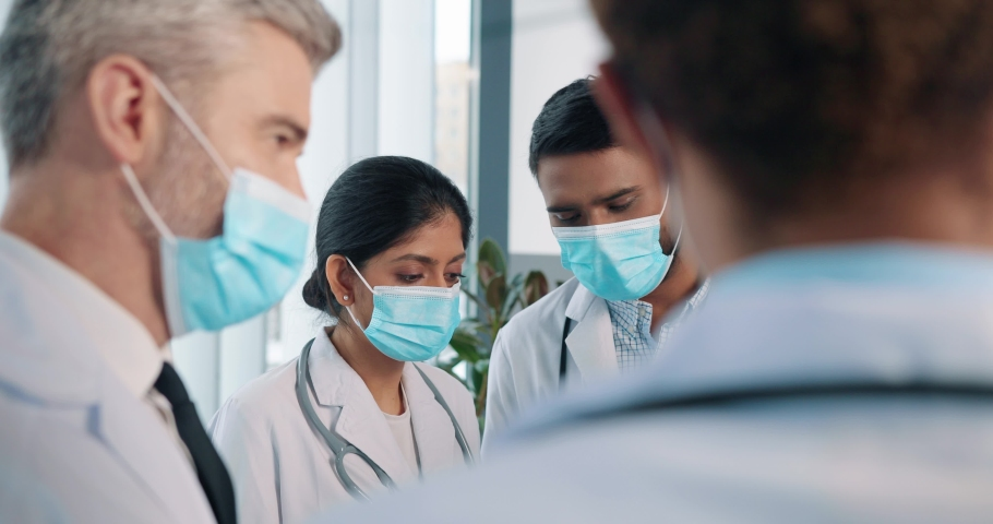 Close up of team of mixed-races medical workers female and male doctors in medical masks stand in hospital talking discussing patient analysis results, typing on tablet, disease treatment concept Royalty-Free Stock Footage #1066881637