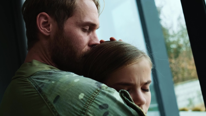 A close-up view of a sad soldier man is hugging his young daughter sitting at home before leaving the family