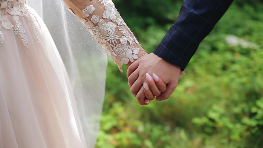 A guy and a girl hold hands on the background of beautiful nature. Taking a close-up of their hands Royalty-Free Stock Footage #1066961143