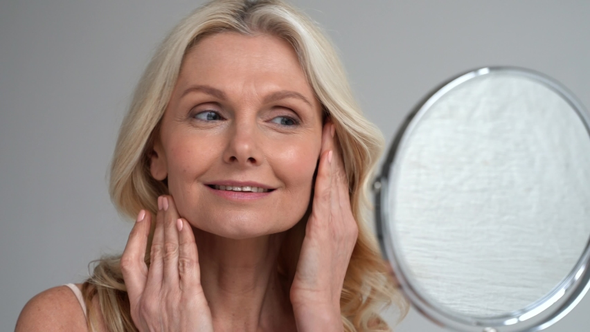 Happy 50s middle aged woman model touching face skin looking in mirror. Smiling mature older lady pampering, enjoying healthy skin care, aging beauty, skincare treatment cosmetic products concept. Royalty-Free Stock Footage #1066964707
