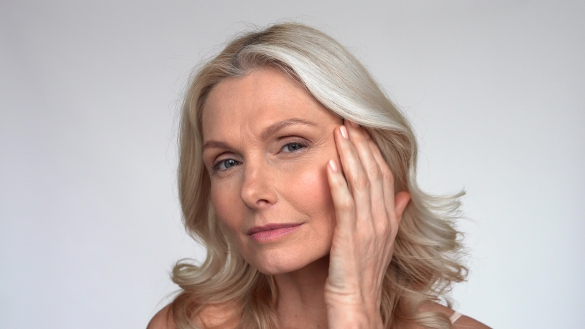 Happy 50s middle aged mature woman touching facial skin looking at camera pampering in mirror. Old healthy dry skin care beauty concept, skincare treatment, cosmetics and anti age plastic surgery. Royalty-Free Stock Footage #1066964725
