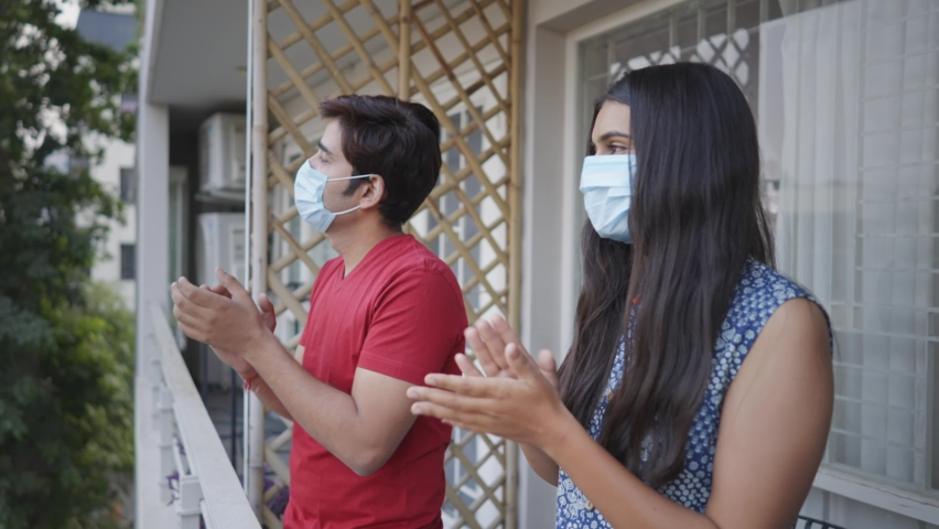 An attractive young couple standing on the balcony and clapping hands to appreciate and salute the work of essential service provider, health workers, police, nurses, paramedical staff, etc Royalty-Free Stock Footage #1066996933