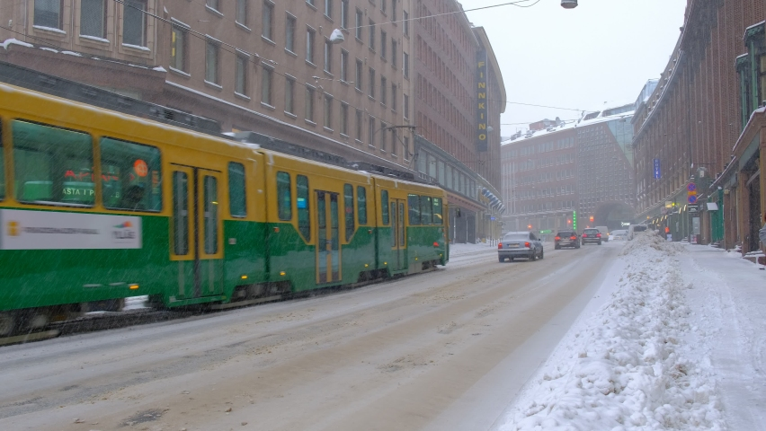 Helsinki, Finland - January 12, 2021: Kaivokatu street during the strong snowstorm. Tram, cars, bus are moving on the snow-covered street.