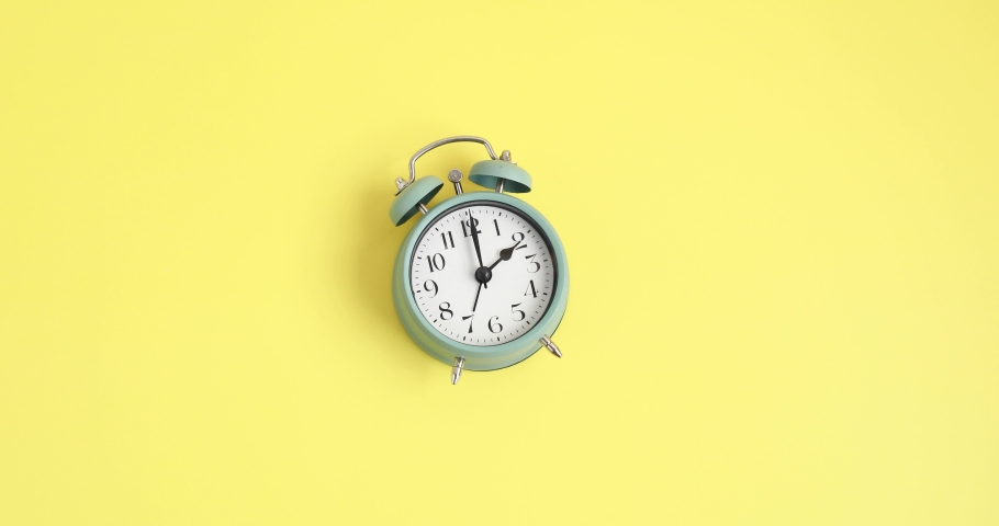 Woman forwarding the clock one hour ahead for daylight saving time ove yellow background Royalty-Free Stock Footage #1067002774