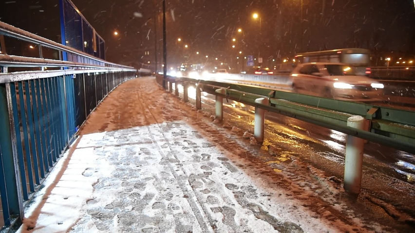 Night winter view of a busy street in big city. Headlights of cars crossing bridge in falling snow. Snow-covered pavement in  headlights of moving cars.
