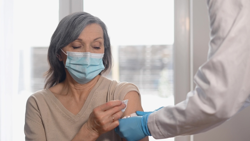 An elderly woman getting a vaccine for coronavirus, a doctor wearing mask and gloves with a syringe makes an injection to a mature senior patient. The concept of confronting the pandemic Royalty-Free Stock Footage #1067020702