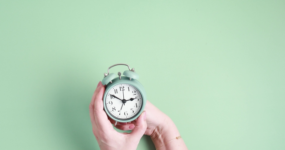 Woman forwarding the clock one hour ahead for daylight saving time ove yellow background Royalty-Free Stock Footage #1067041471