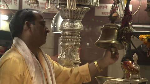 AGRA, INDIA - OCTOBER 23, 2010: Man ringing bell during Puja ceremony in Kalka temple