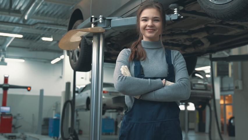 Mechanic female posing looking at camera in a car workshop. International Women's Day.    Shutterstock HD Video #1067082286