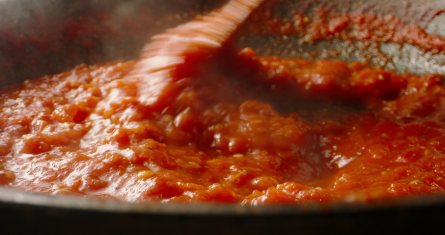 Tomato sauce boiling in a pan, being stirred with a spoon. Hot tomato sauce cooked for pizza or pasta. Italian cuisine, food and drink 4k footage