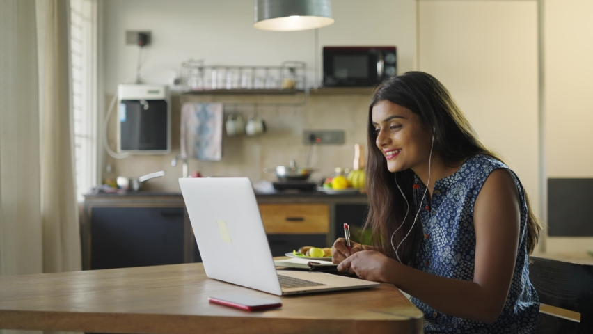 A young beautiful woman is sitting on a chair and writing down or taking down notes while attending an online video class or office meeting in an interior house set up. Work from home concept Royalty-Free Stock Footage #1067145055