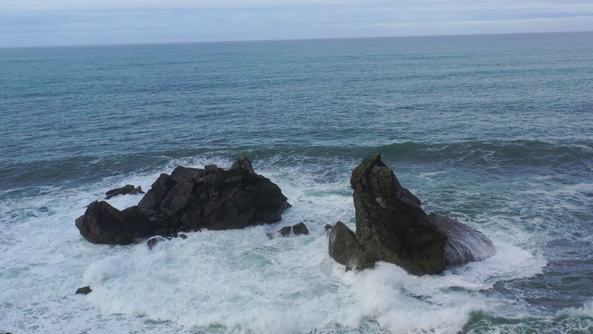 The cold waters of the Pacific Ocean crash on the rocky Northern California coastline in Humboldt. The scenic Pacific Coast Highway runs along this amazing and rugged part of the west coast. Royalty-Free Stock Footage #1067154217