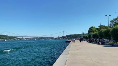 ISTANBUL - CIRCA JULY, 2019: Footage of people walking and relaxing by Bosphorus strait in Emirgan area of Istanbul. FSM bridge is in the view. Beautiful scene. It is a sunny summer day. Camera moves.