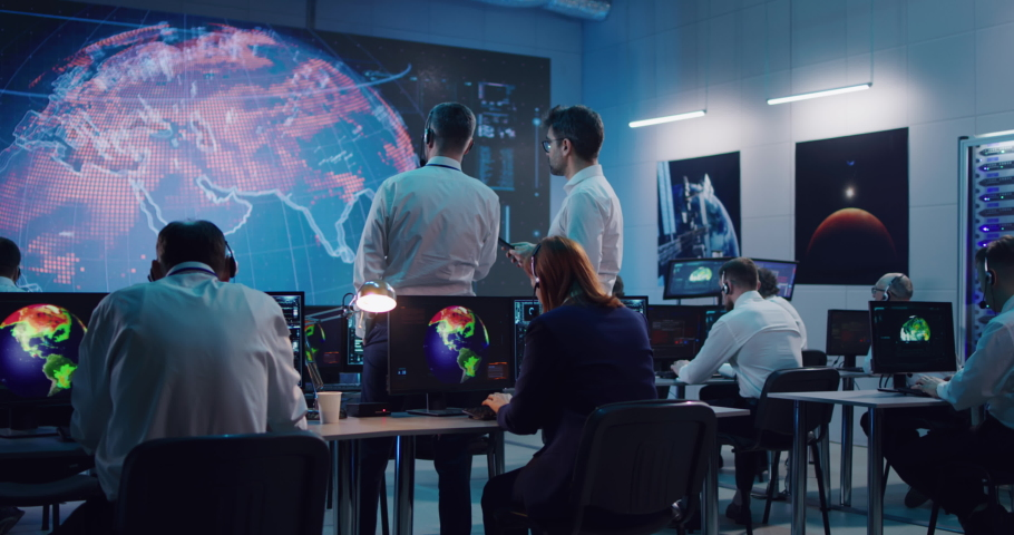 Zoom out view of men discussing data on tablet and large screen while working on global warming problem in ecology control center Royalty-Free Stock Footage #1067179126