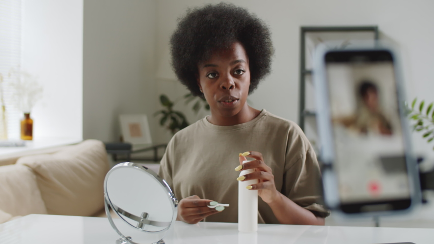 Young beautiful Afro-American woman sitting at table in living room, looking at smartphone camera and showing how to apply lotion to facial skin with cotton pad while recording video for beauty vlog | Shutterstock HD Video #1067226175