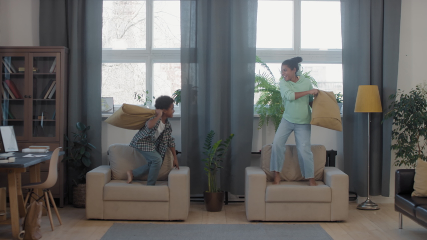 Full shot of two cute mixed-race siblings standing on soft armchairs in living room by windows, having fun together while pillow-fighting | Shutterstock HD Video #1067235013