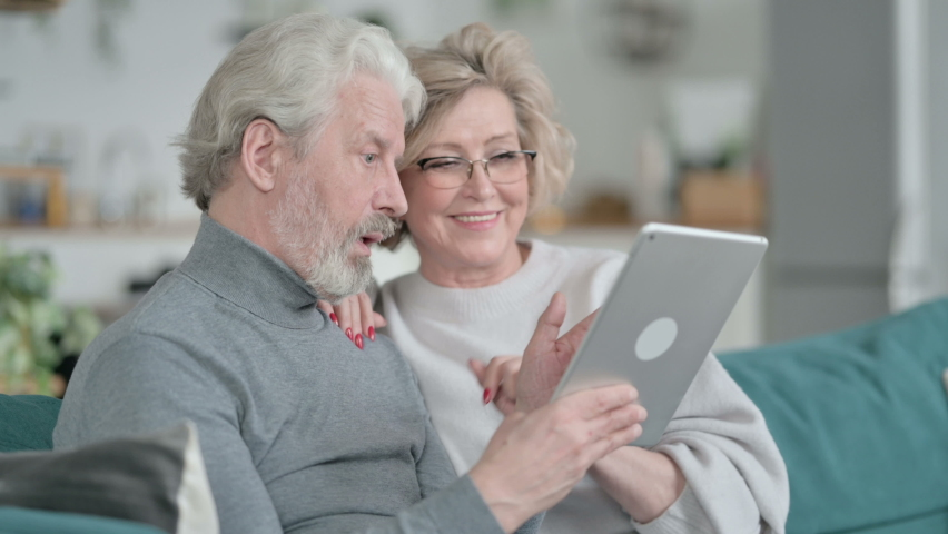 Happy Old Couple Sitting on Sofa and using Tablet | Shutterstock HD Video #1067241265