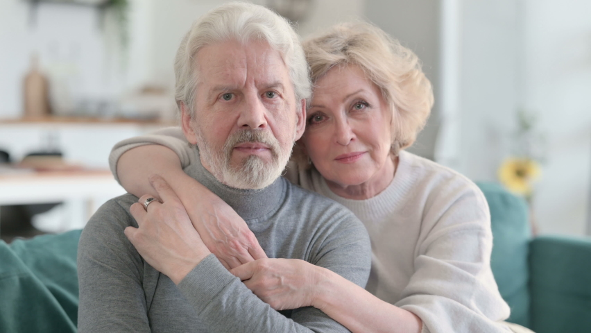 Embracing Senior Old Couple Smiling at Camera while Sitting on Sofa  | Shutterstock HD Video #1067241274