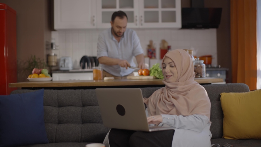 A young woman in hijab, working from home, describes what she should do to her husband, who prepares a meal in the kitchen. Remote working concept. Royalty-Free Stock Footage #1067247295