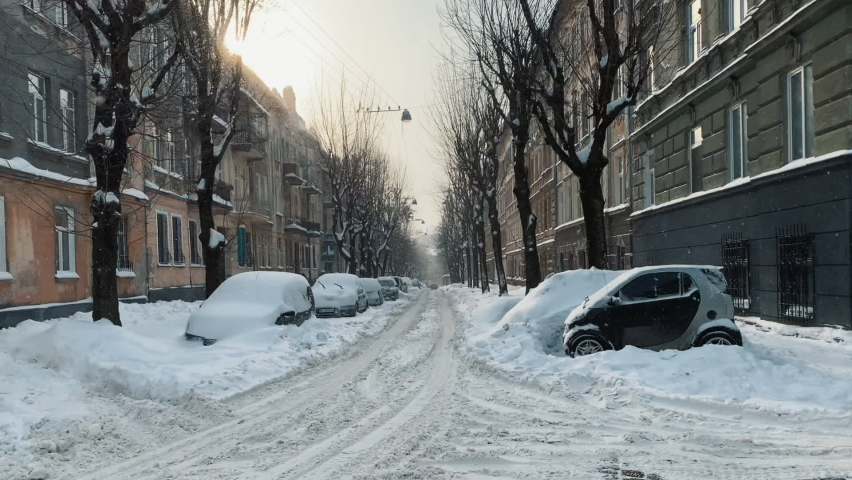 Winter in the city. snow covered trees, cars, road. The road is in the snow, in the air a lot of snowflakes are flying. Heavy snowfall in the city streets, houses and machine snowy.