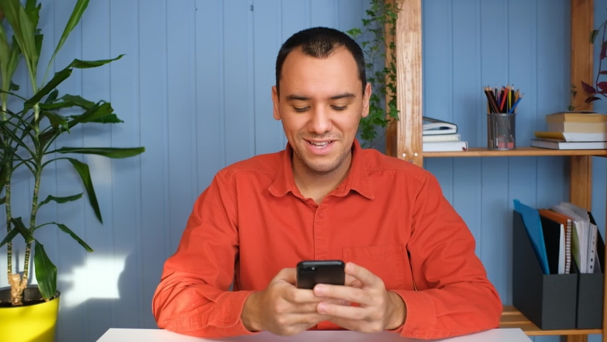Young man holding modern smartphone texting message in office. Royalty-Free Stock Footage #1067287993